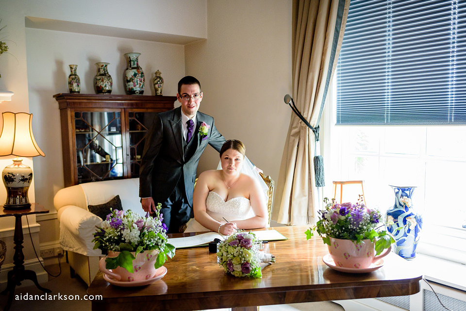 a photo of the couple signing the register at hemswell court wedding venue